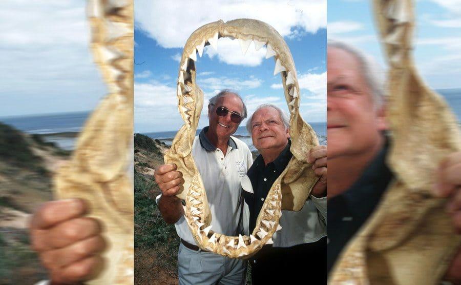 Rodney Fox and David Jason holding up a shark's jaw