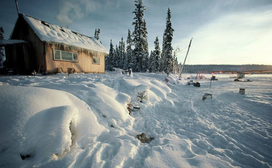 A small wooden cabin in the cold snowey planes on Alaska