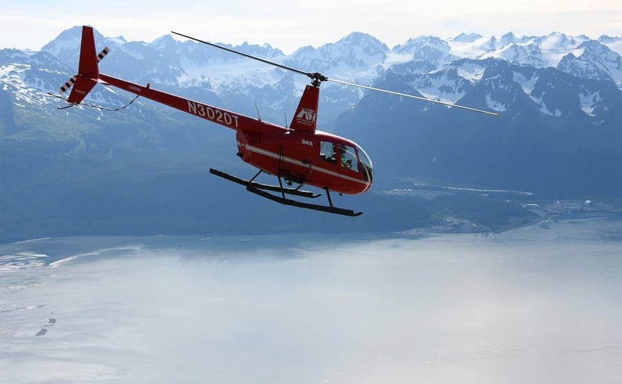 A red helicopter flying over the the great lakes of Alaska.