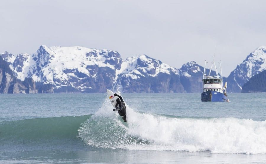 Surfer rides the waves with the Alaskan mountains as his backdrop.