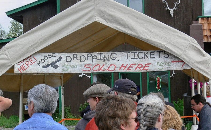 The line in front of the sign to get tickets for the moose dropping festival, would you wanna pay to collect moose poop?