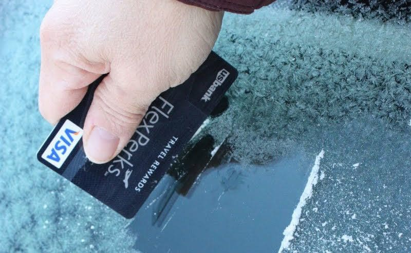 Cleaning the ice off a windshield by using a credit card to scrape it off.