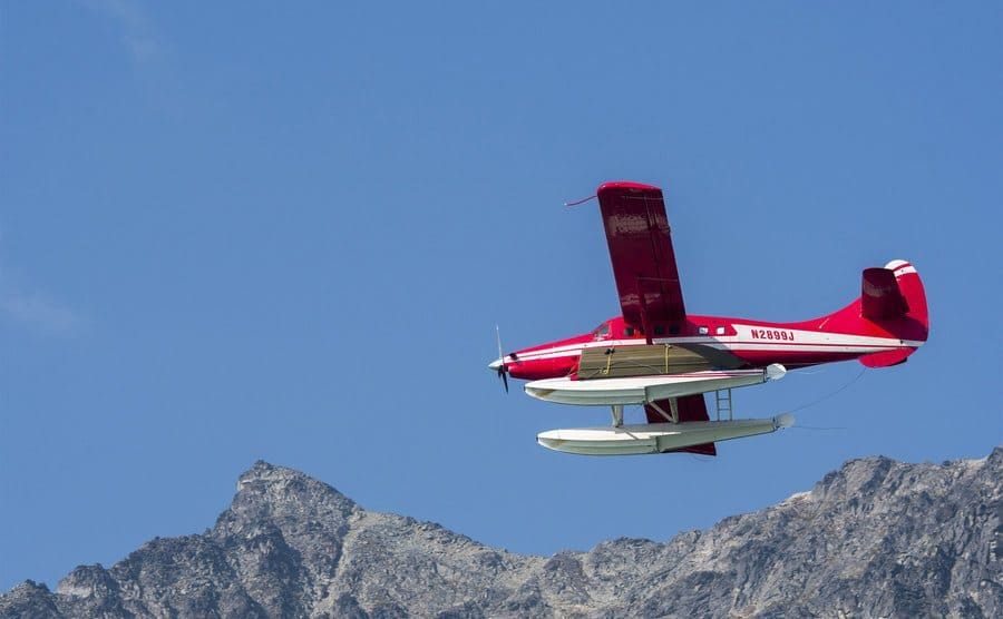 A red seaplane is flying over Lake Crescent in Lake Clark National Park and Preserve Alaska.