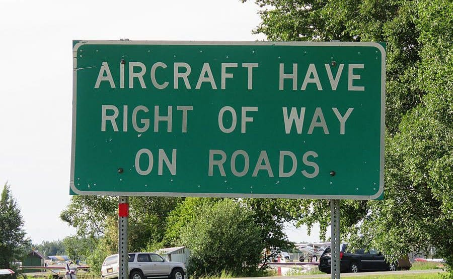 A traffic road sign that tells you to give right of way for aircrafts on the road.
