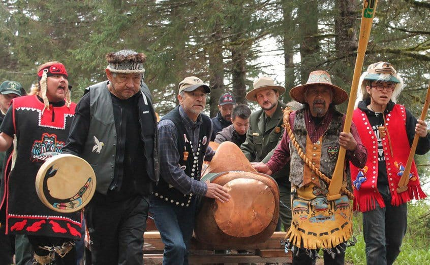 Alasken natives marching in traditional garmits in the woods as part of a ceremony.