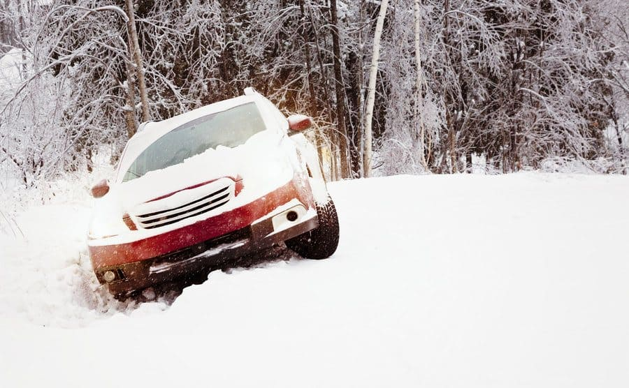Snow covered car stuck in a ditch.