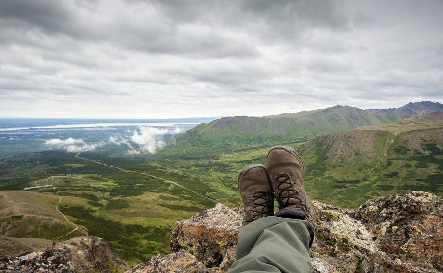 Climbers legs and feet on top of Flat Top Mountain trail, near Anchorage, Alaska.