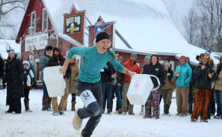 A woman competing in the festivities and racing with two jugs in her hands.