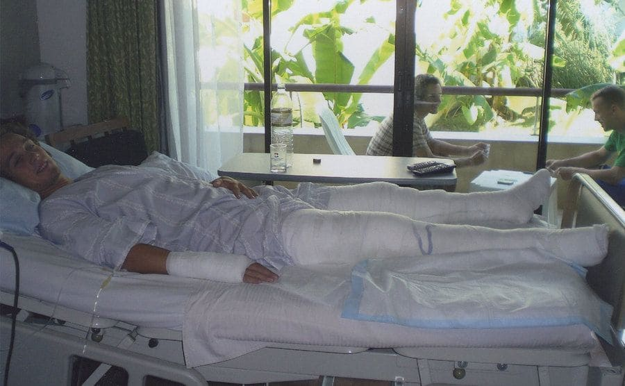 Colin O'Brady sitting in a hospital bed with his legs bandaged up