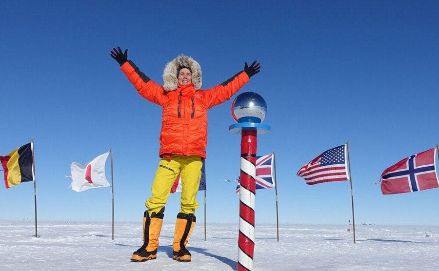 Colin O'Brady standing in snow gear in front of a large white and red striped pole with a glass ball on it and flags from different countries around it in the snow.