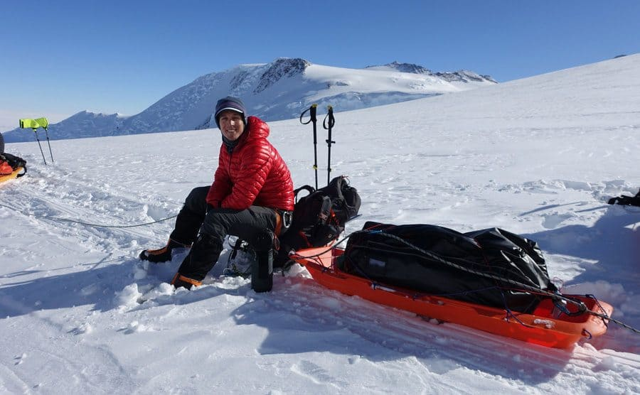 Colin O'Brady sitting on the edge of his sled with his ski gear and tent in the middle of the snow-covered mountain