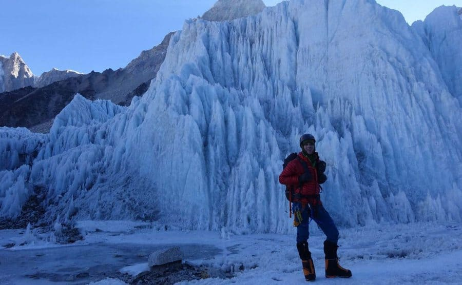 Colin O'Brady posing with his gear in front of a large ice cliff