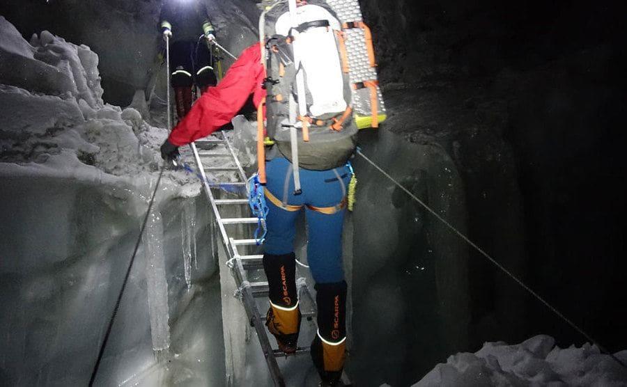 Colin O'Brady crossing over a gap in the ice in the dark
