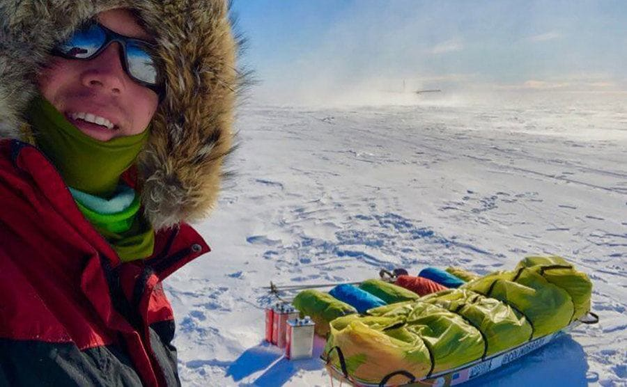Colin O'Brady taking a selfie with two sleds filled with gear in an area covered in snow
