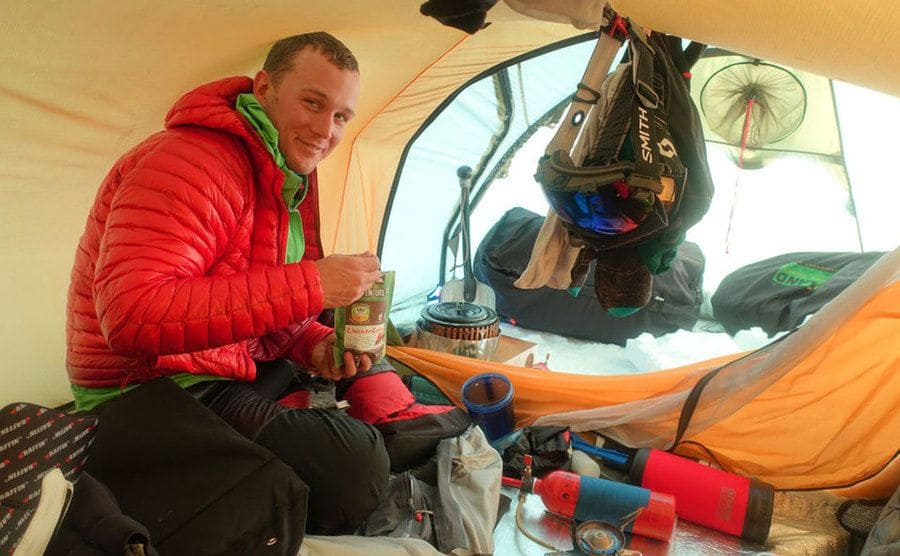 Colin O'Brady eating a snack in his tent