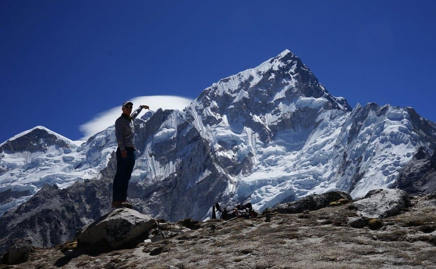 Colin O'Brady pointing to the tip of Mount Everest from a mountaintop nearby