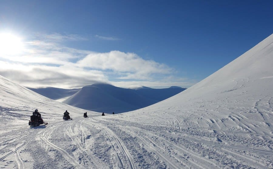 Colin O'Brady and other people on snowmobiles riding in between small mountains