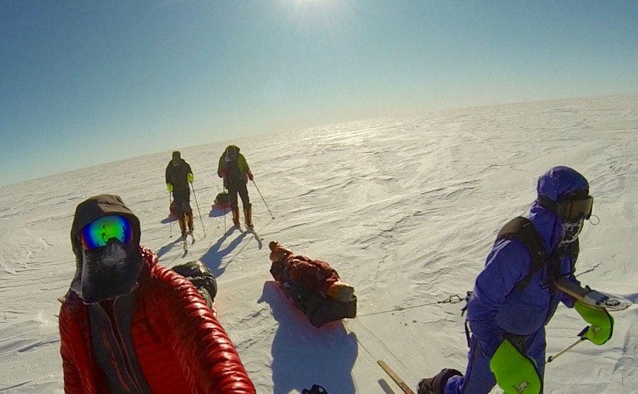 Colin O'Brady with other skiers on a flat snowy ground dragging their gear on sleds