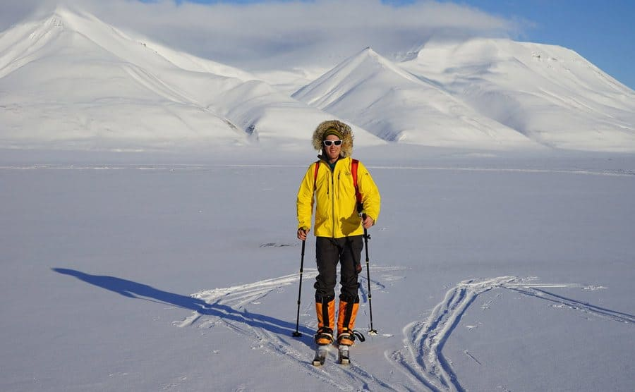 Colin O'Brady standing in skis on the flat snowy ground