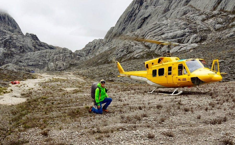 Colin O'Brady in a valley with a helicopter next to him