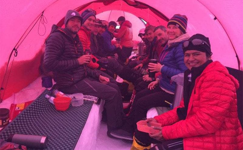 Colin O'Brady with other hikers eating together inside of a tent