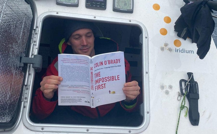 Colin O'Brady reading his book titled The Impossible First while sitting in the side of a boat