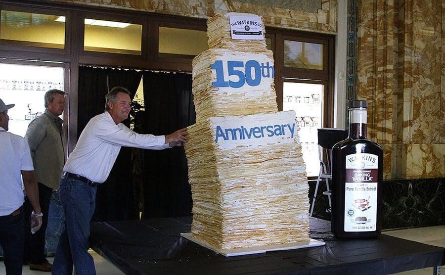 This 150 layer cake stands so tall that it needs the support of a full grown man so that it wont tip over.