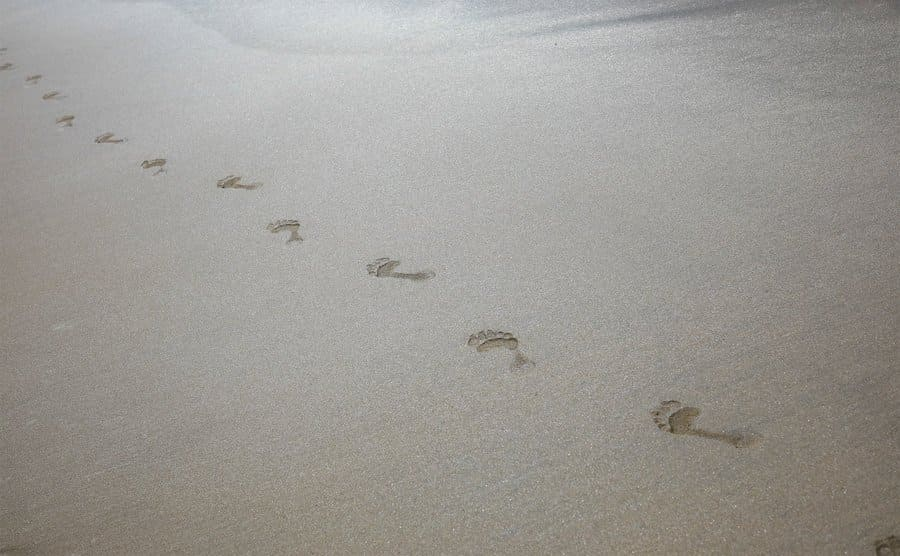 Bare footprints in the sand walking away.