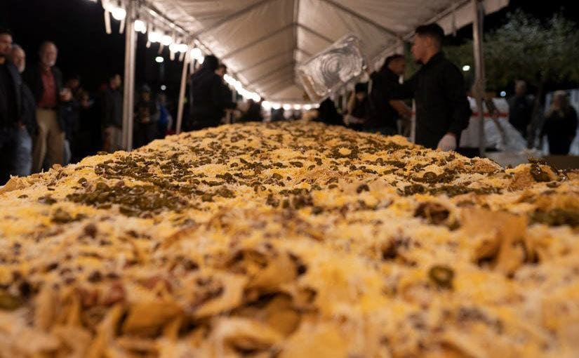 A long table covered on every inch by nachos and toppings.