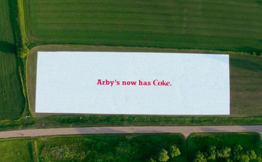 """Arial view of the giant Arby'e sign, it says """"Arby's now has Coke"""" in red on a white background."""