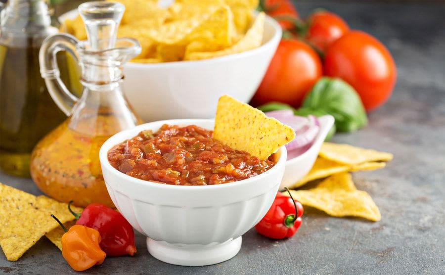 Tortilla chips dipped in a bowl of salsa.