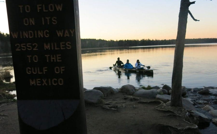 Three Teammates canoeing along the Mississippi river in their canoe.