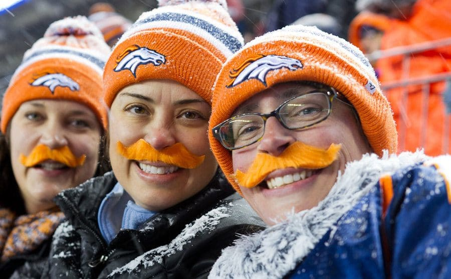 Three Bronco fans with orange mustaches stuck on their faces at a game.