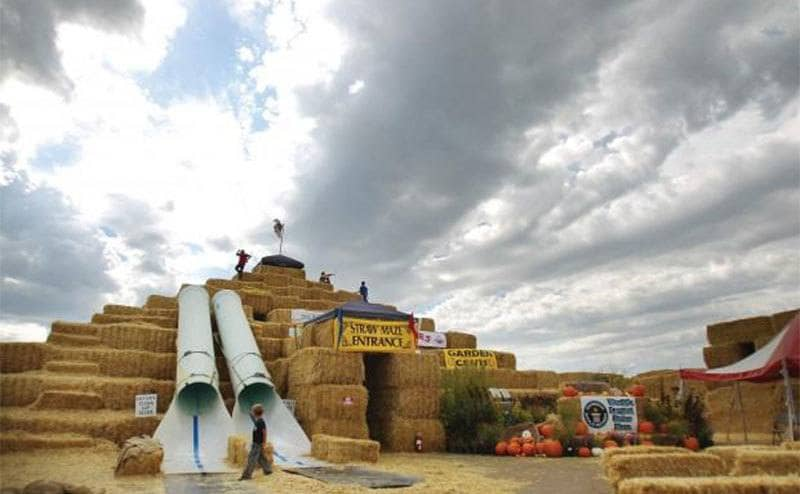 A three story bale maze entrance shaped like a pyramid with slides coming down it and children playing everywhere.