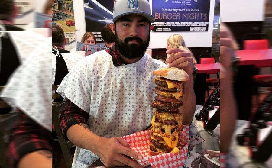A man sitting at a table, wearing an apron about to eat an over foot tall hamburger stack with cheese and sauces.