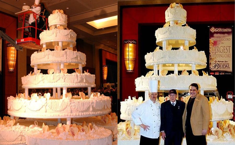 The wedding cake standing so tall you need a crane to get to the top / three men standing before the very large wedding cake, they're pretty small in comparison.