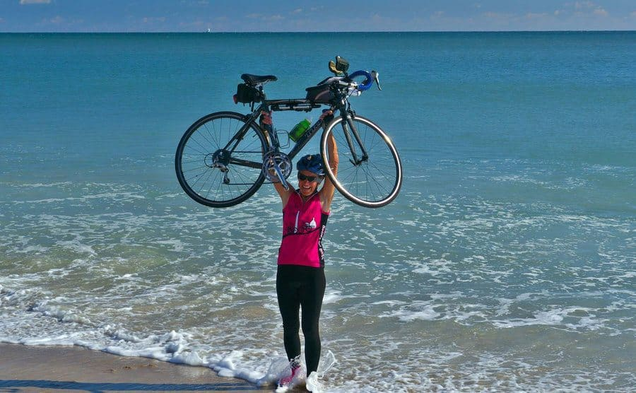 Salvo holding her bike triumphantly over her head on the beach.
