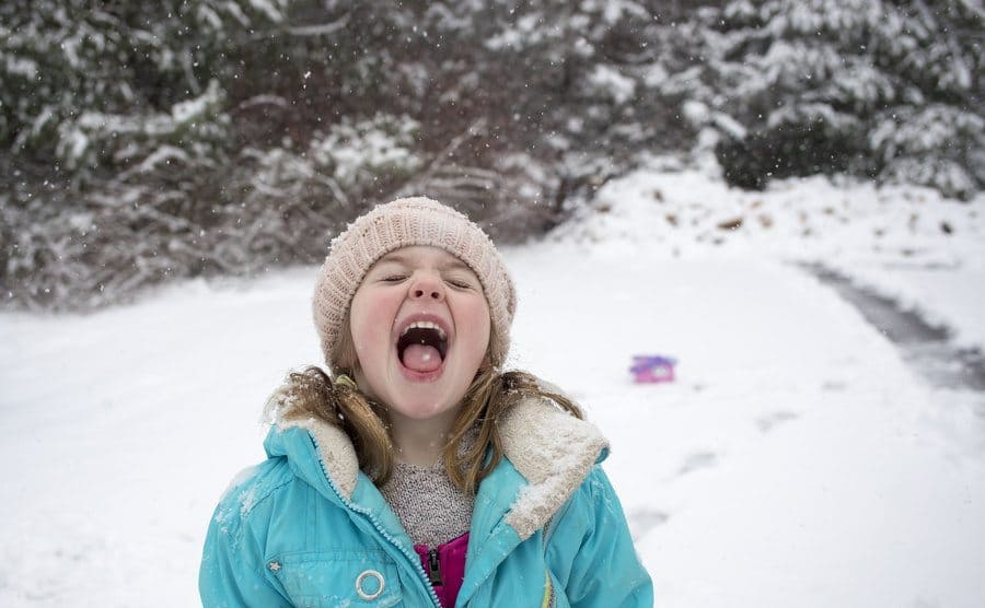 A little girl trying to catch a snowflake in her mouth.
