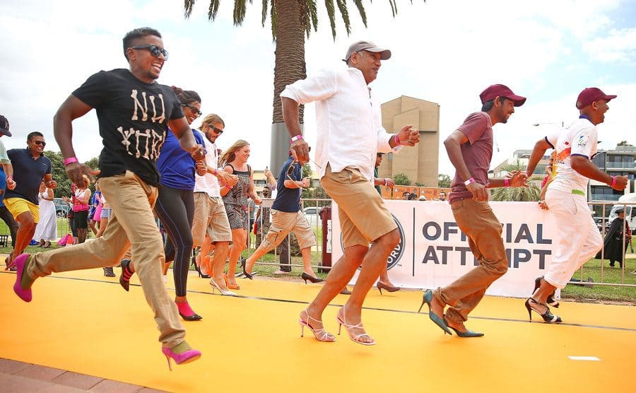 Men and Women wearing high heeled shoes take part in a Guinness World Record attempt for the largest amount of people running in high heels.