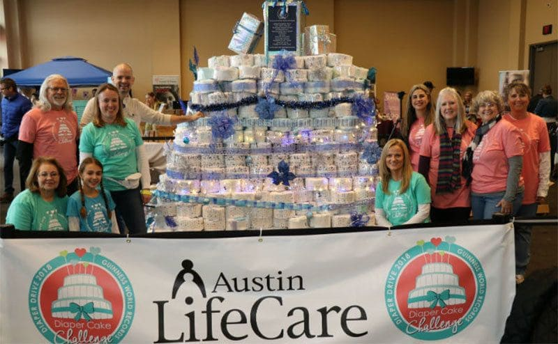 A group of women standing around a multitiered diaper cake covered in lights and ribbons.