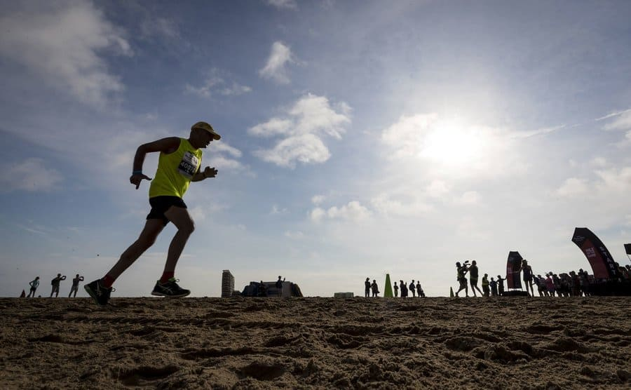 The silhouette of a man running as part of a race on the sand.