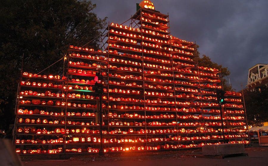 Thousands of lit jack-o-lanterns standing stacked on display, setting the mood for Halloween.