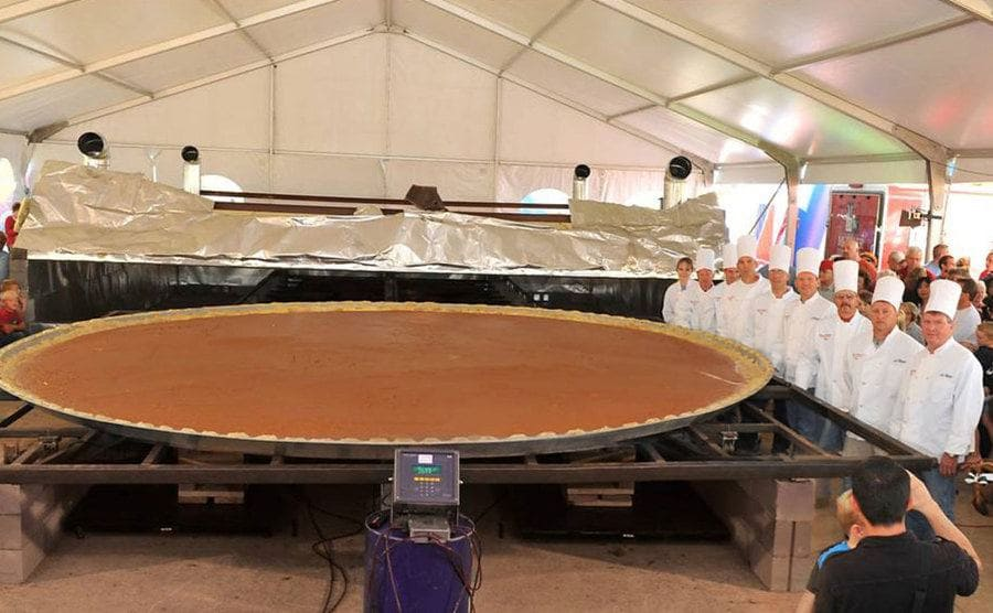 All the chefs who made this pie standing victoriously next to it at the Pumpkinfest.