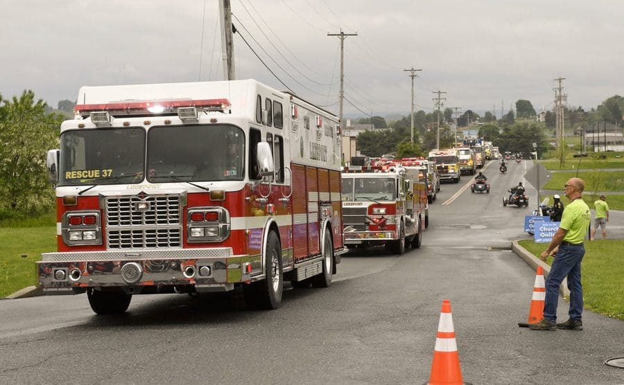 A parade of fire trucks moving down a road.