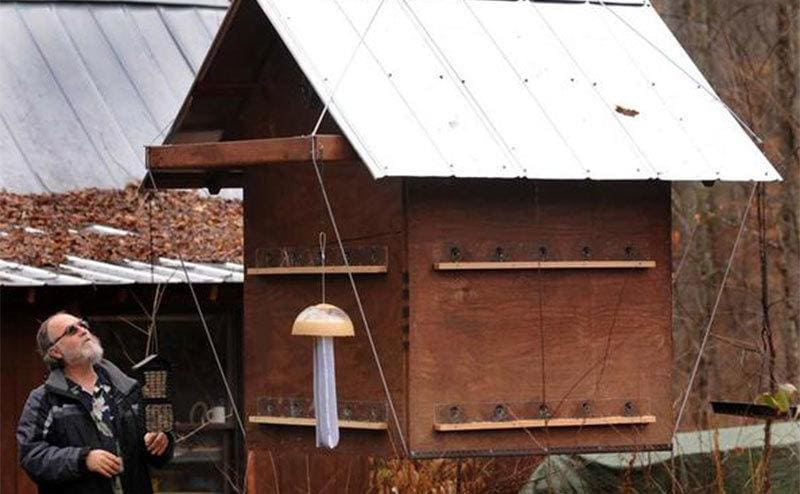 William Greene standing next to this birdfeeder, it's bigger than a doghouse.