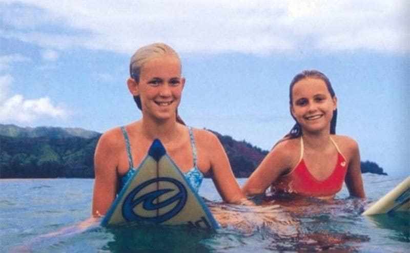 A young Bethany and friend on surfboards in the middle of the ocean.