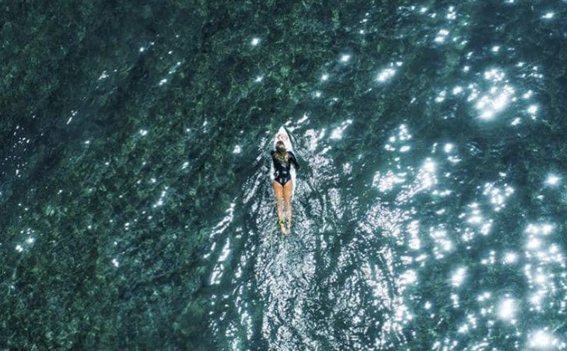 An aerial view of Bethany on a surfboard out in the middle of the ocean, all alone.