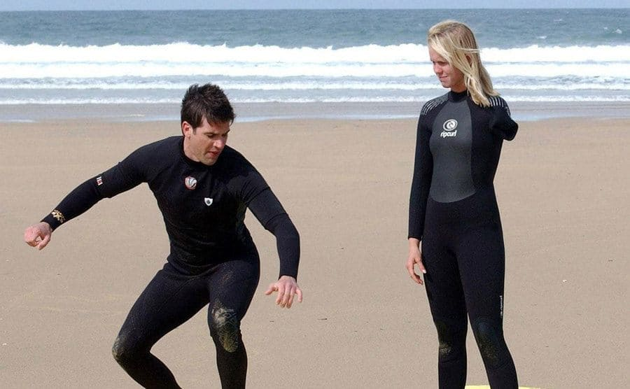 Bethany is standing on the beach as part of a surfing lesson alongside a young man.