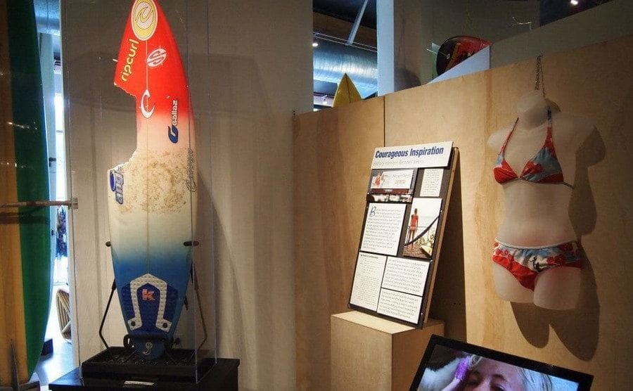 Bethany's surfboard with the shark bite and bikini set on display in a museum.