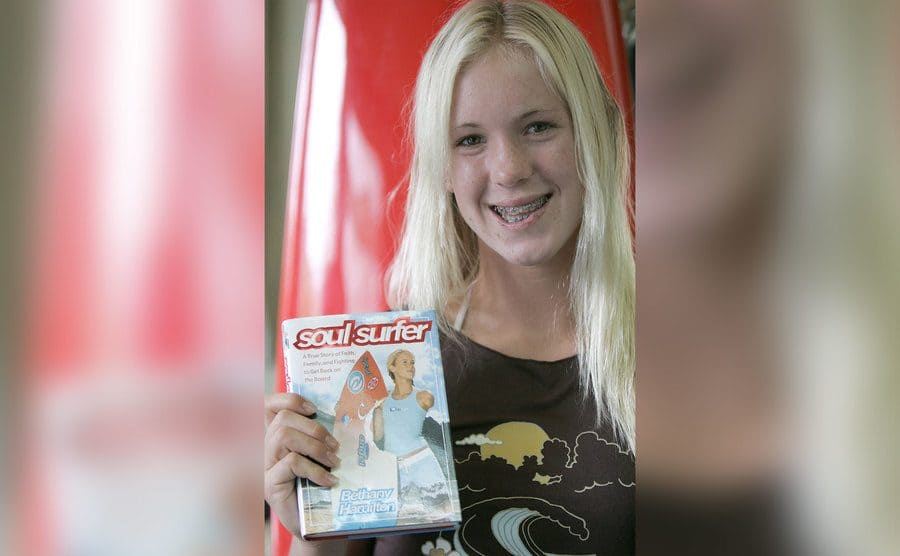 14-year-old Bethany is holding up a copy of her book.